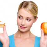 woman choose  from sweet cake and red apple